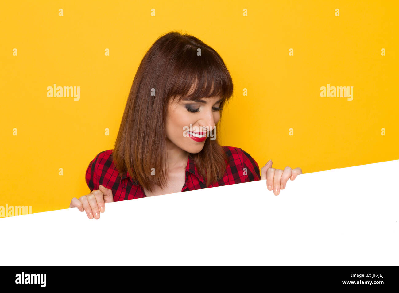 Smiling young woman posing behind white copy space looking down and reading. Head and shoulders studio shot on yellow - Stock Image