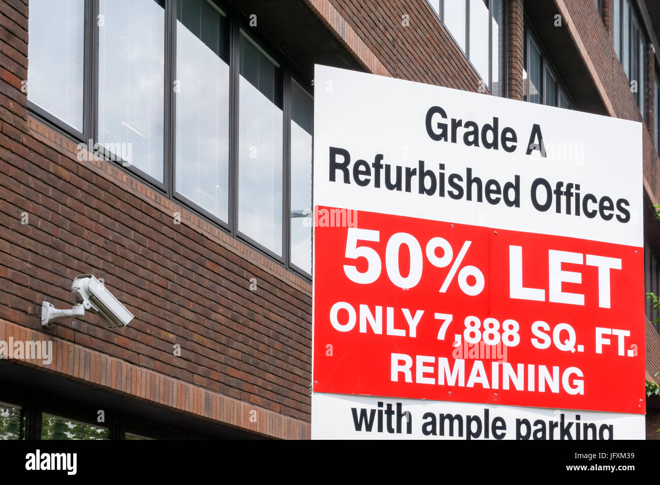 Sign for refurbished offices to let, with office building behind - Stock Image