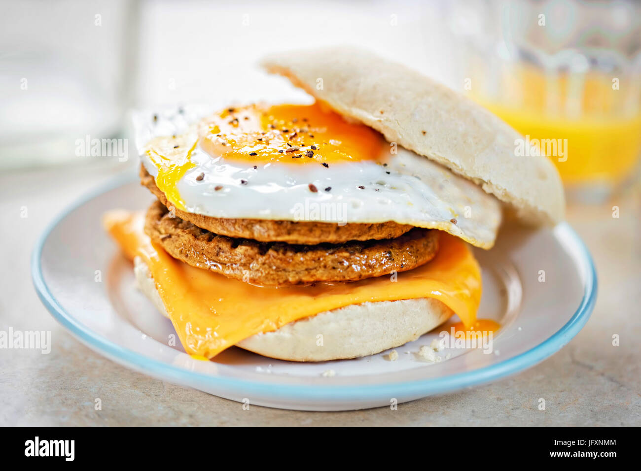 Meat free sausage flavour patties with cheese and egg on breakfast muffin - Stock Image
