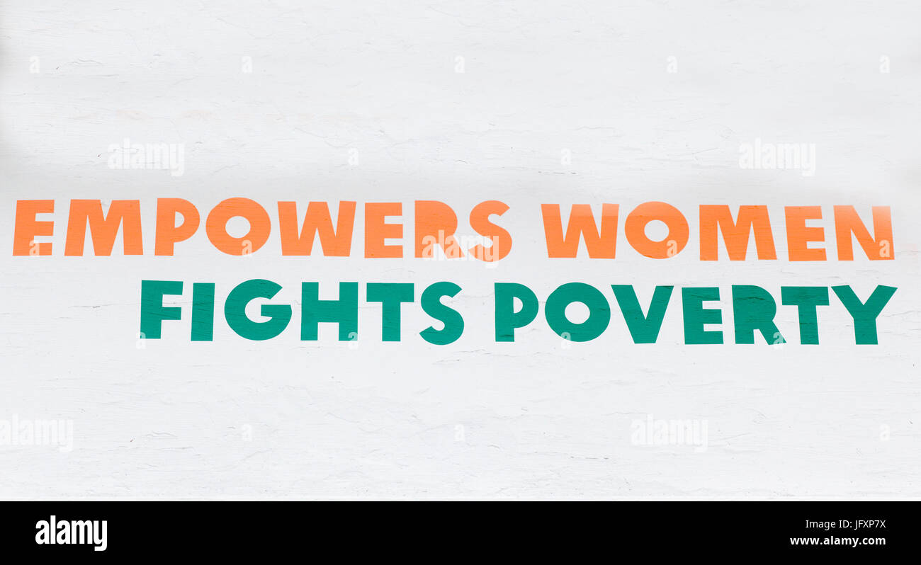 Empowers women, fights poverty sign - Stock Image