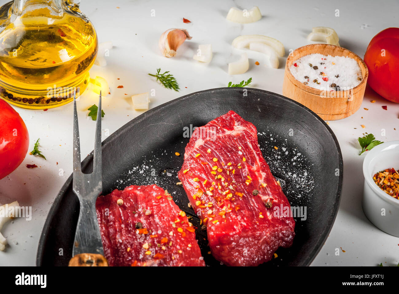 Meat, beef. Fresh raw steaks in a frying pan. Spices (salt, pepper), fresh vegetables - tomatoes, carrots, garlic, onions. On a white marble table, wi Stock Photo