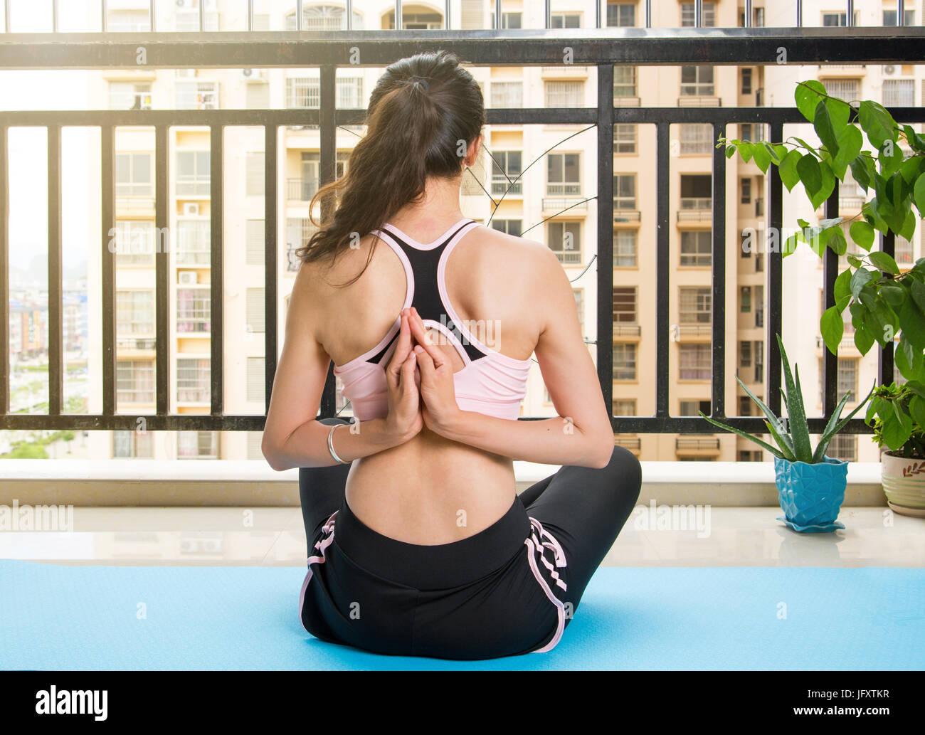 Girl doing Pashchima namaskarasana, Reverse Prayer yoga pose - Stock Image