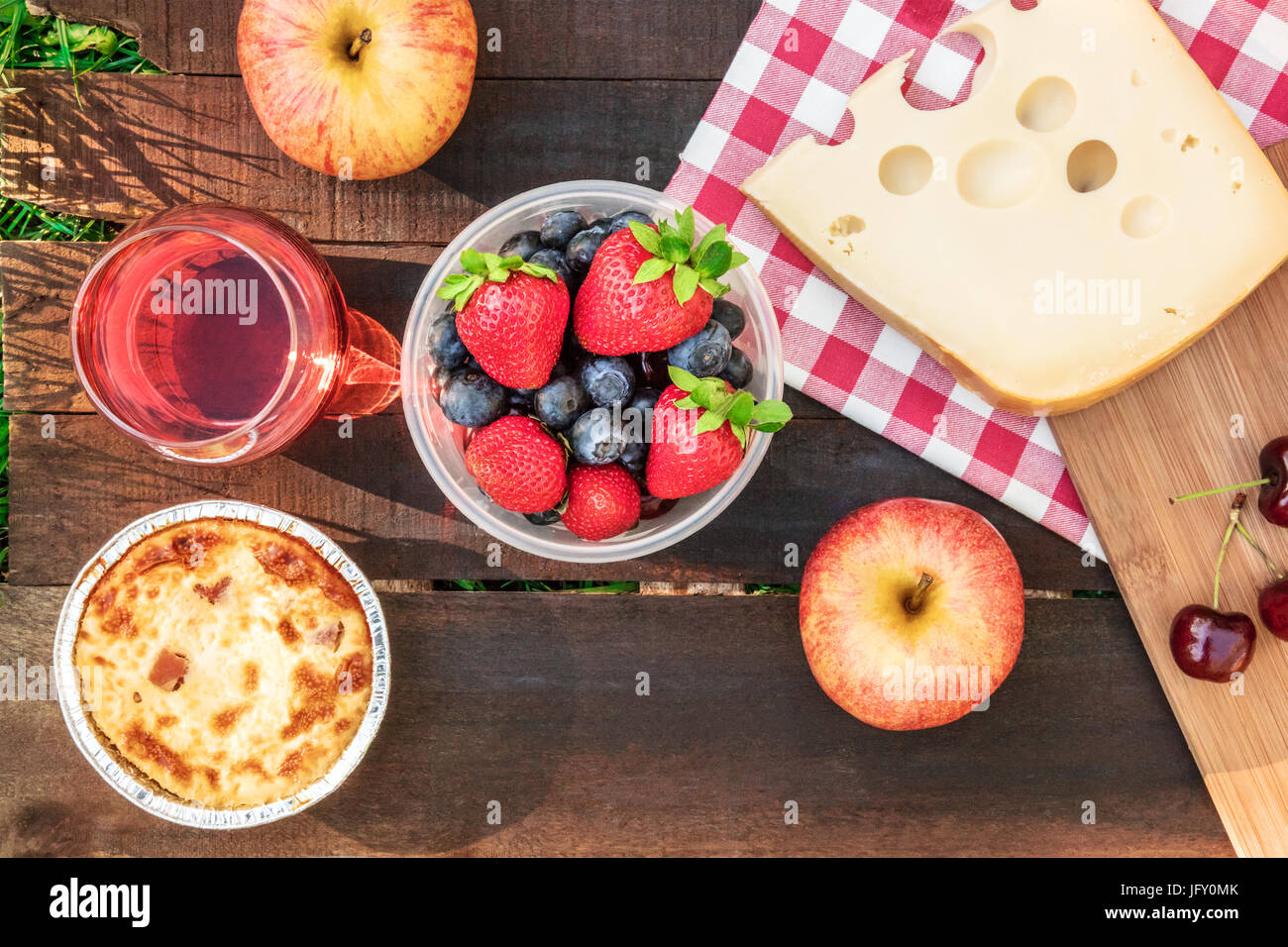 Overhead photo of picnic with apples, glass of rose wine, fresh fruit in plastic container, quiche, and piece of - Stock Image