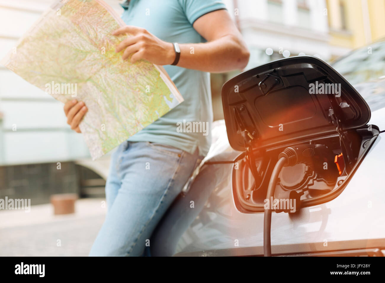 Young man planning itinerary while car being charged - Stock Image