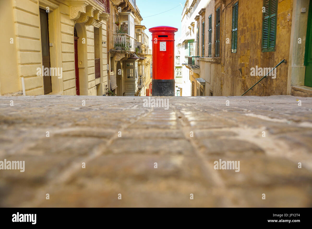 A photograph of an old British postbox standing in Valletta, Malta. The old stone buildings of Valletta surround - Stock Image