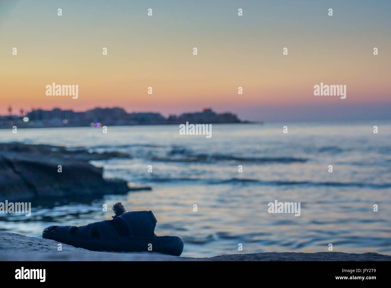 An image of a single flip flop left on the waters edge in Silema, Malta. The sunset creates an amazing backdrop, - Stock Image
