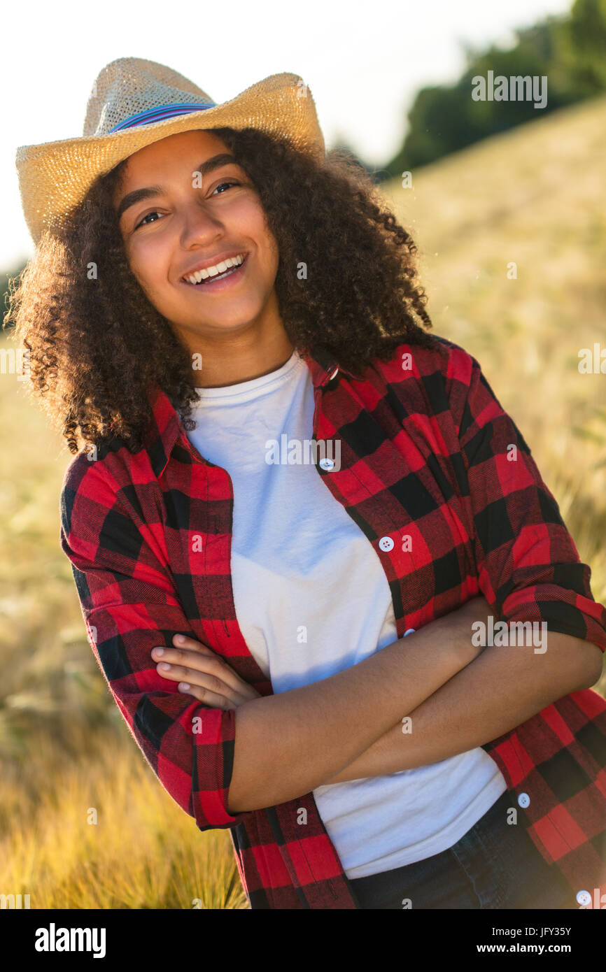 aae27652f452f Portrait of beautiful and happy mixed race African American female girl  child wearing straw cowboy hat