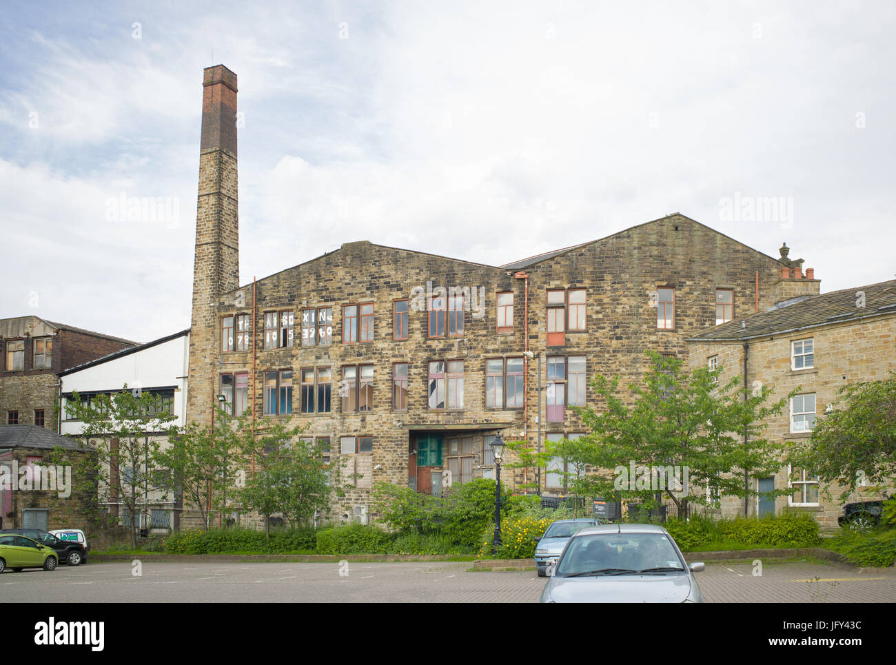 Chimney of former mill with building repurposed and occupied as training school, Burnley, Lancashire, UK - Stock Image