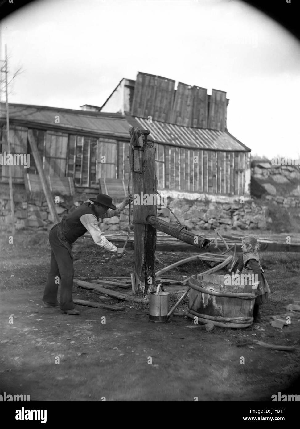En man som pumpar vatten och en liten flicka vid en gammal pump. Ca 1880-1890. Eriksbergsområdet, Stockholm - Stock Image