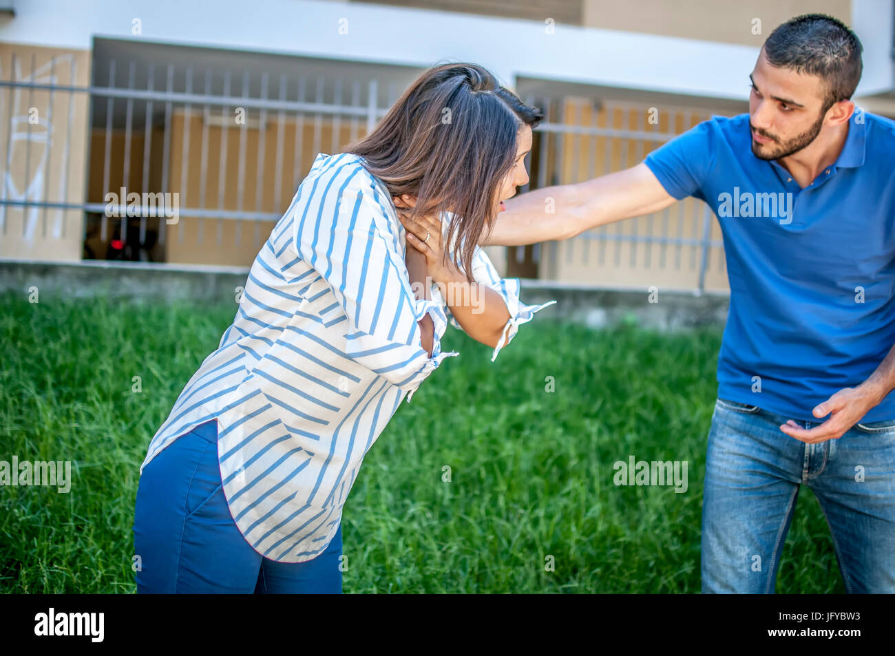 guy trying to help a girl while she's choking - Stock Image