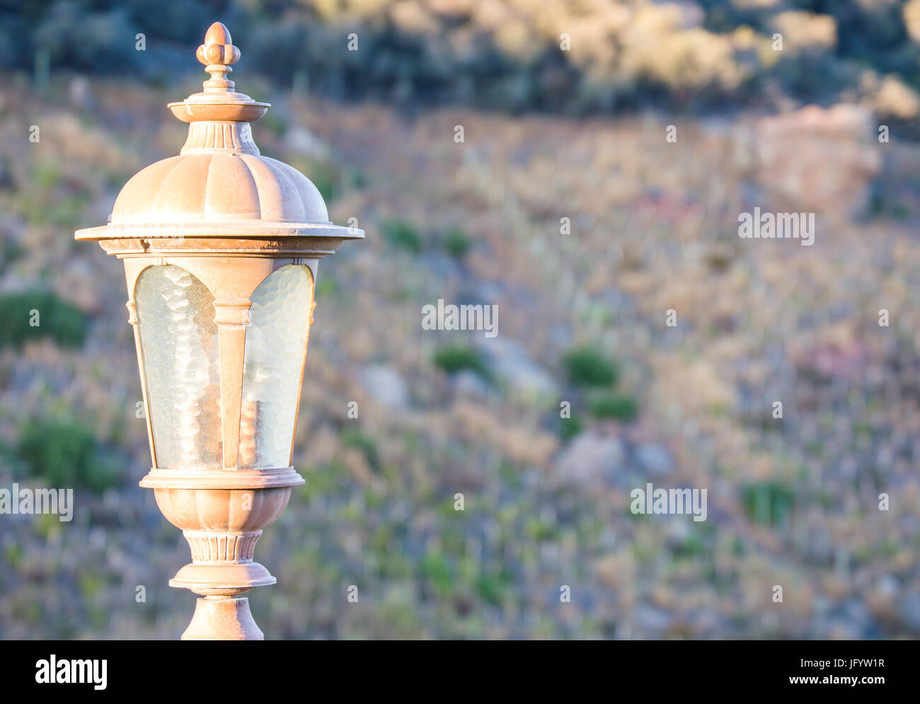carriage lamp on hillside at sunset - Stock Image