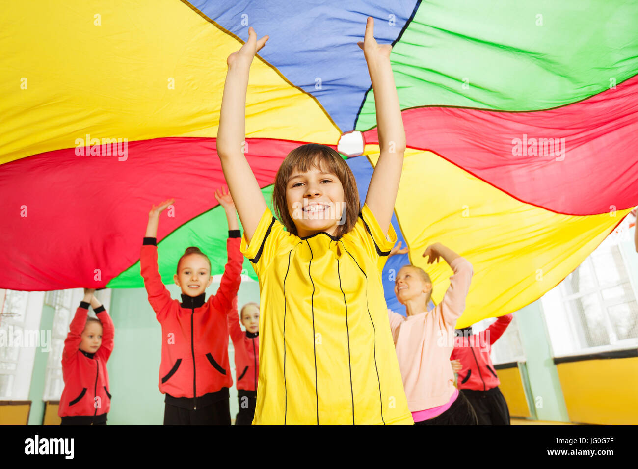 Portrait of smiling preteen boy standing under the canopy made of rainbow parachute with his hands up - Stock Image