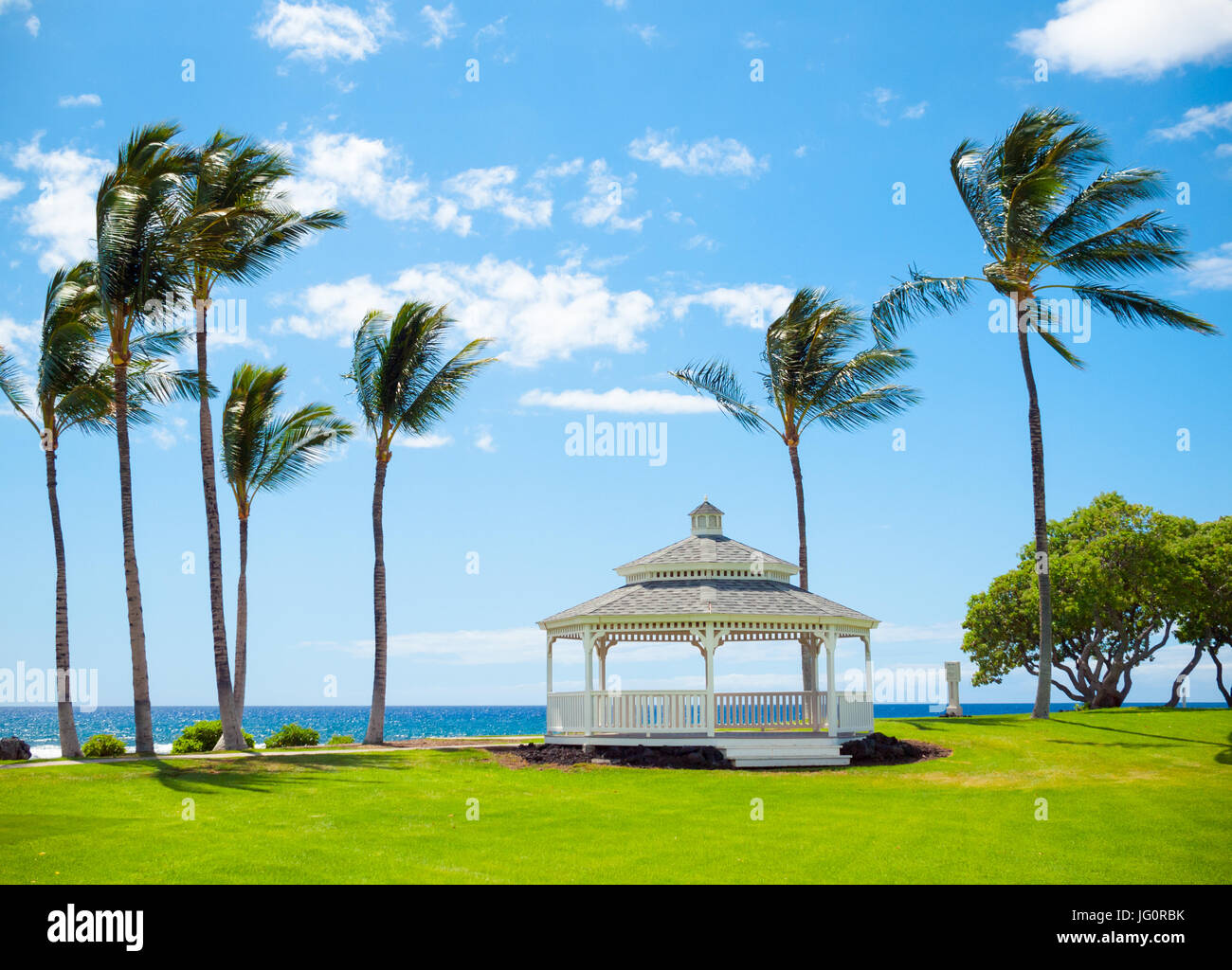 A view of the gazebo, breezy coconut palm trees, and Pacific Ocean at Turtle Pointe at the Fairmont Orchid on the - Stock Image