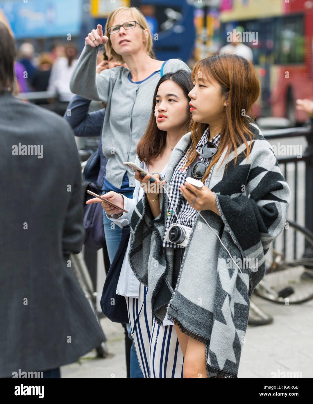 Young Japanese tourists in a busy city in the UK. Stock Photo