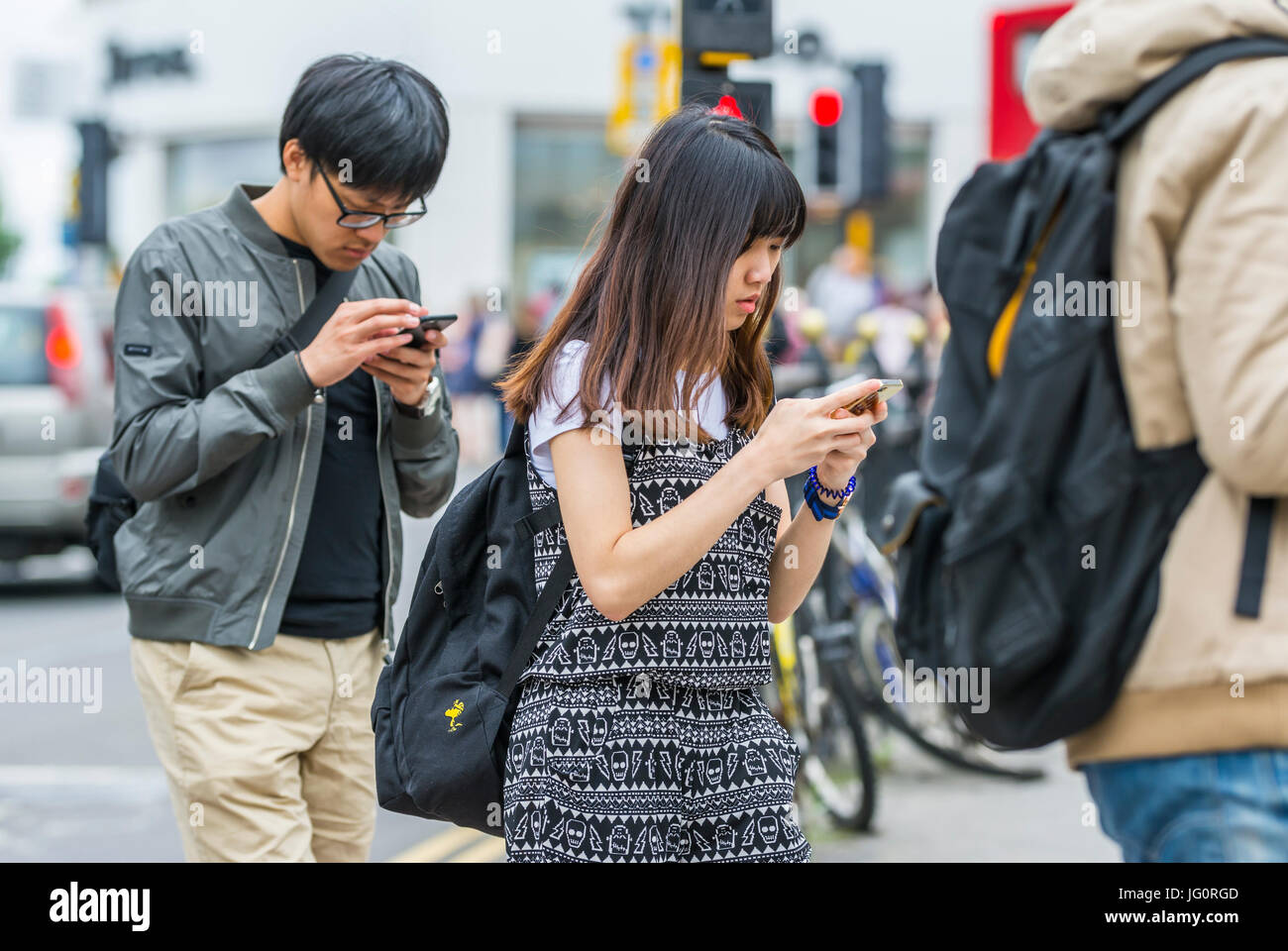 Always connected concept. Japanese tourists walking in a city while looking down and using their smartphones. - Stock Image