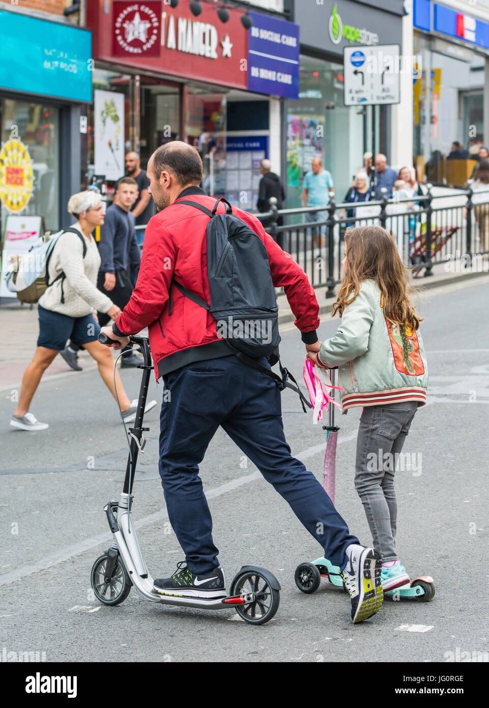 Father and child crossing a road on scooters. - Stock Image