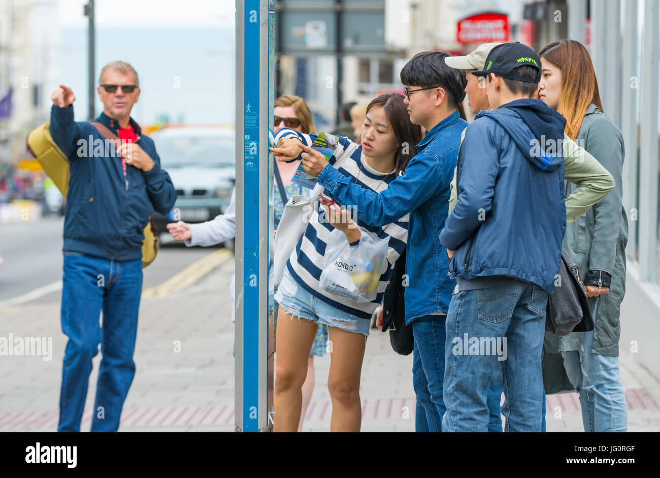 Japanese tourists looking at a street map in a city to find directions. - Stock Image