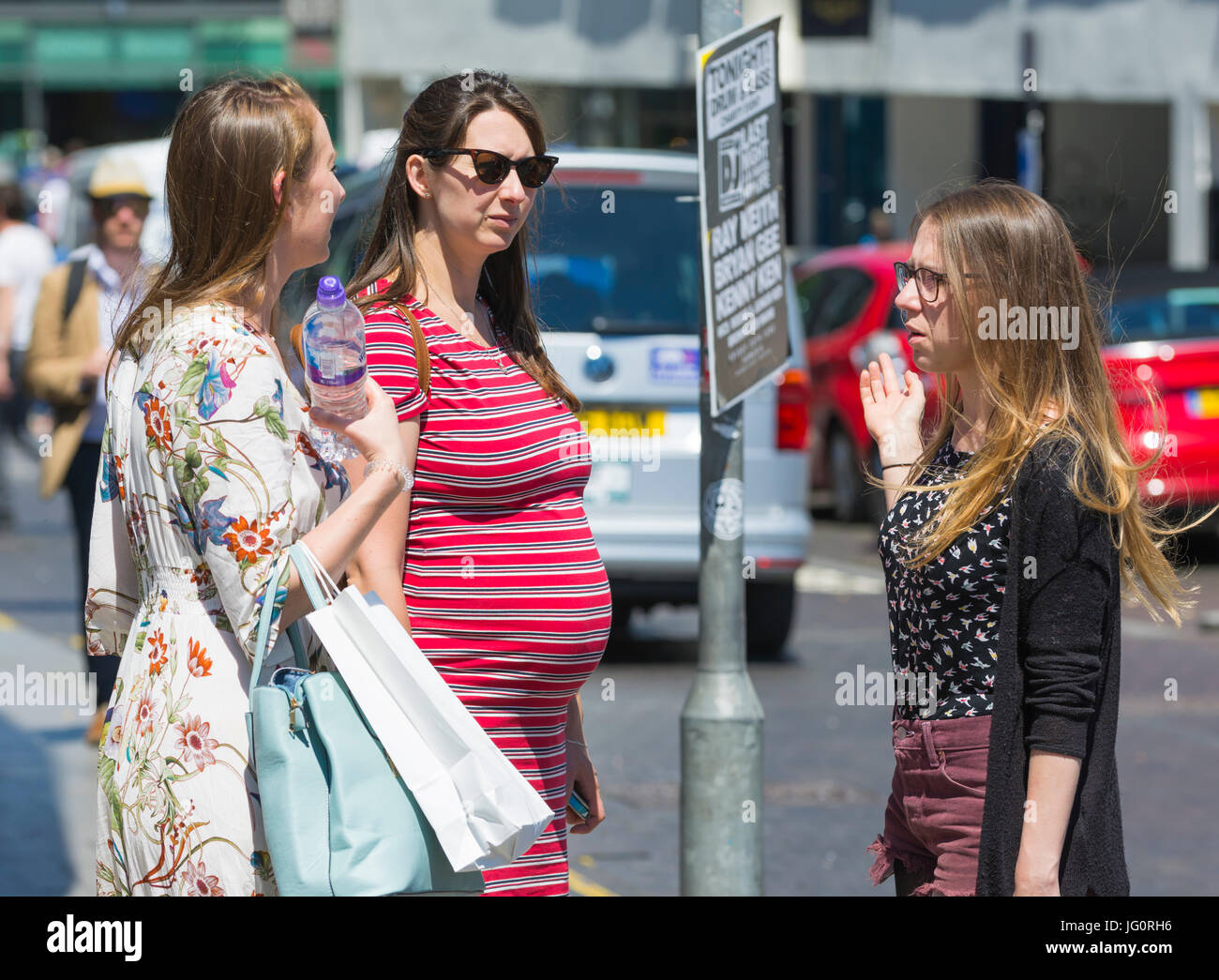Pregnant woman standing in a city speaking to female friends. - Stock Image