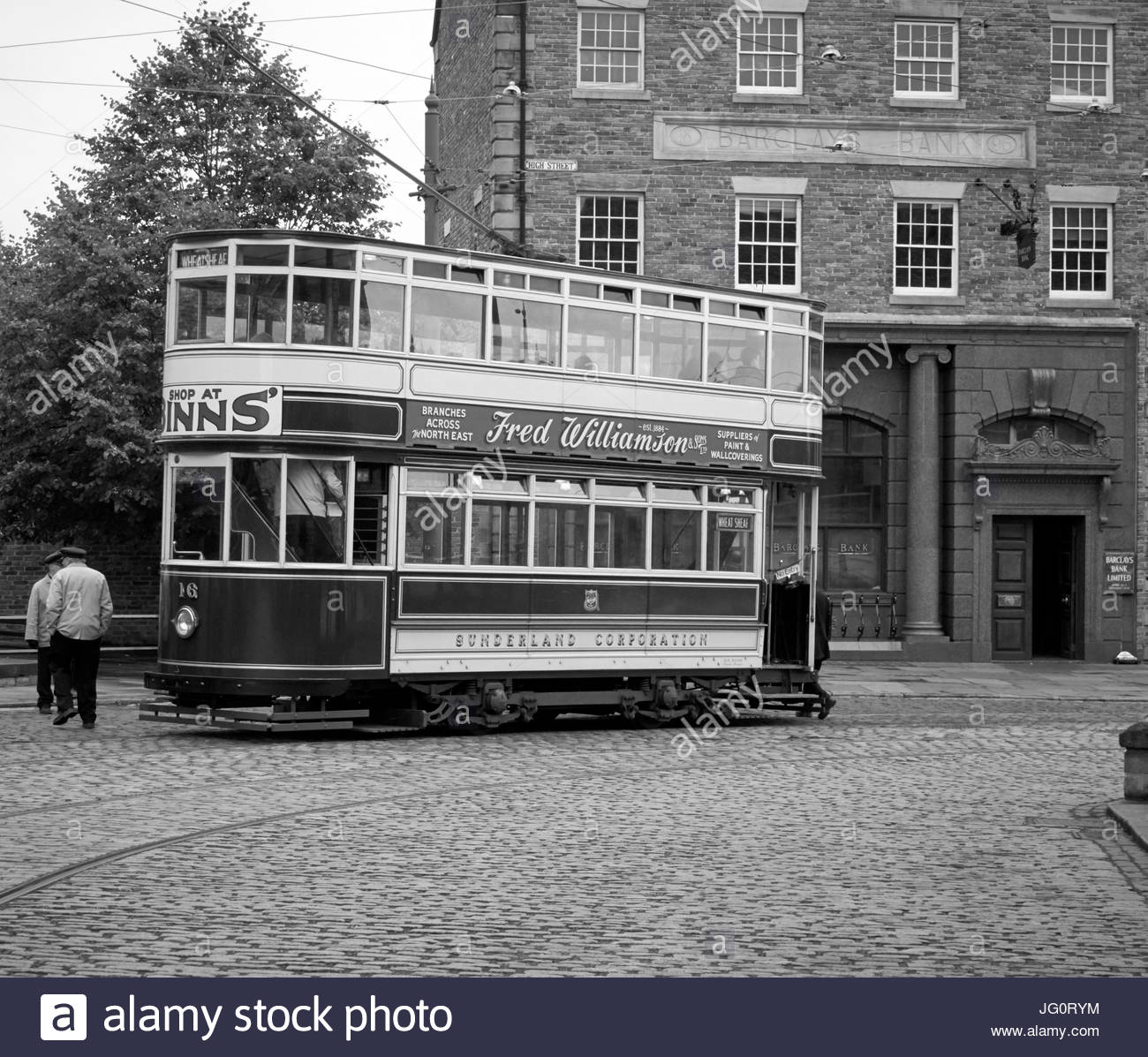 A Sunderland Corporation electric tram stopped outside Barclays Bank in Beamish open air museum in Durham England - Stock Image