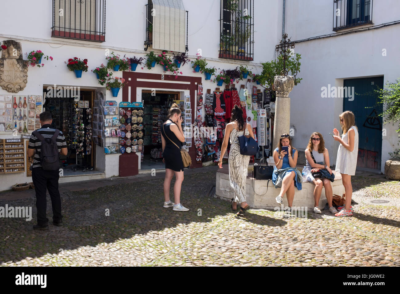 Tourists in the small square in the Calleja de las Flores, Cordoba, Spain. Stock Photo