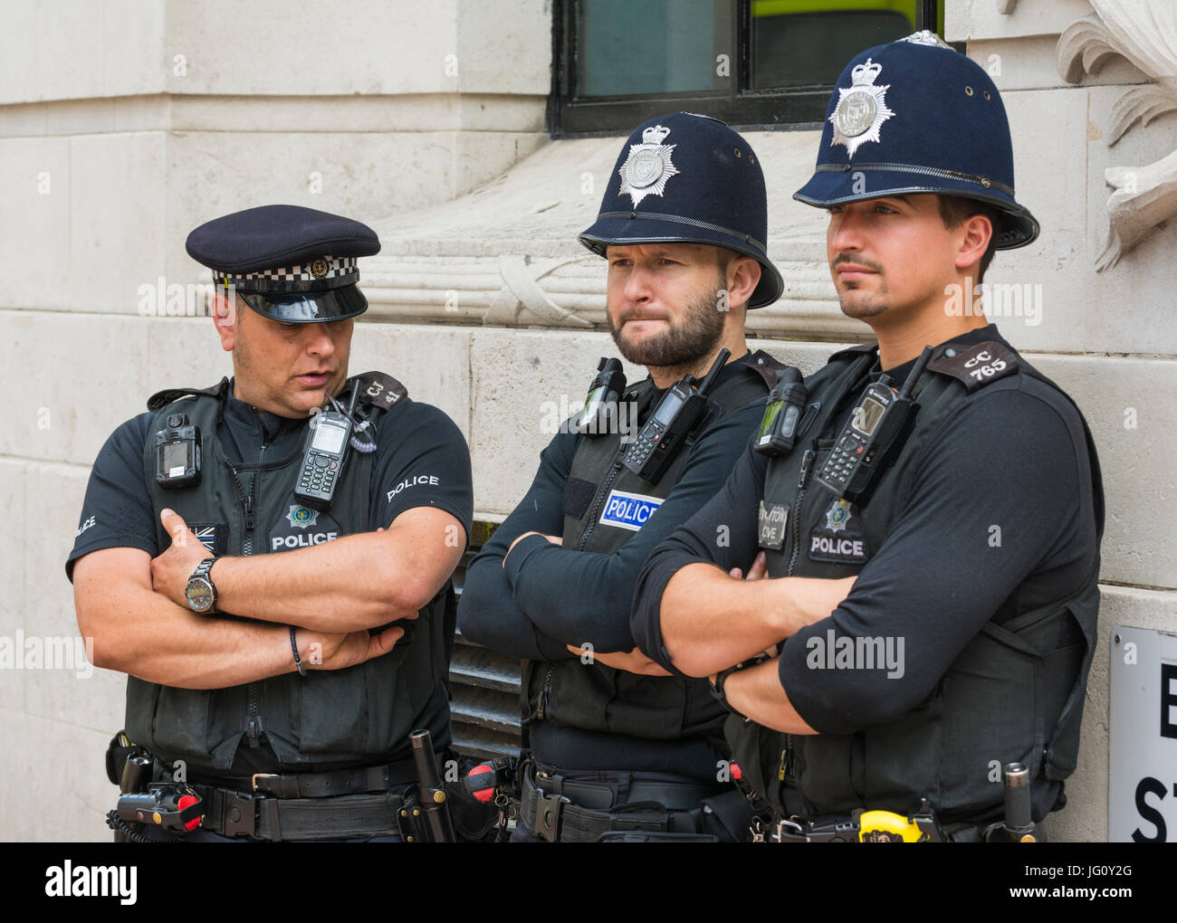 Police officers standing against a wall at a public event in the south of England, UK. - Stock Image