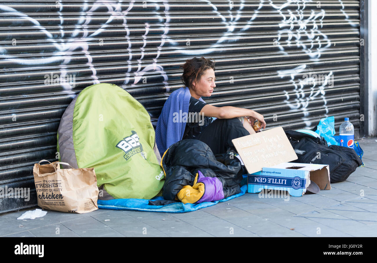 Homeless woman sitting outside on the streets in Brighton, East Sussex, England, UK. - Stock Image