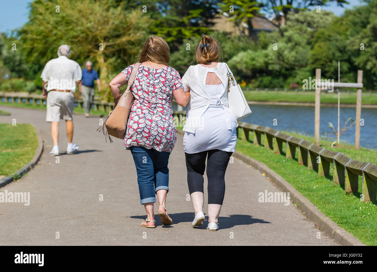 Female friends linking arms while walking through a park by a lake on a warm summer's day. Stock Photo