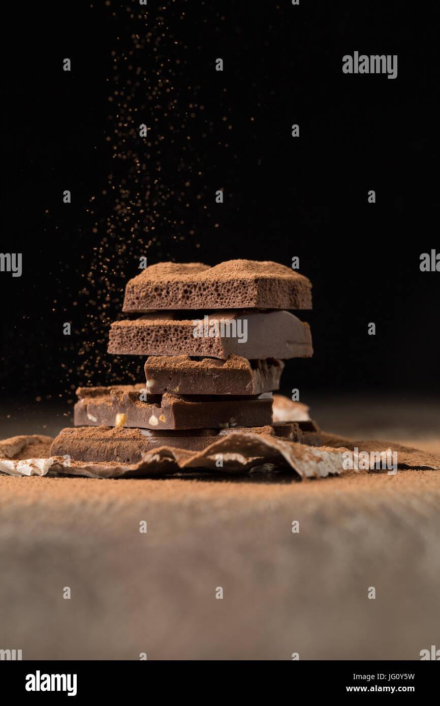 Broken chocolate on bakery paper - Stock Image