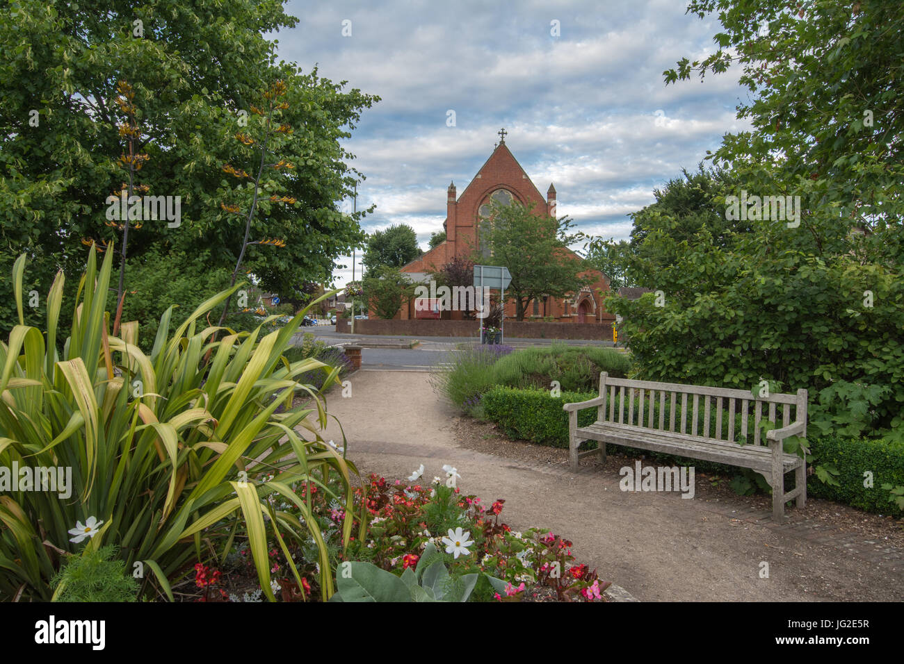 St Mark's Church in Farnborough, Hampshire, UK, in summer with flowers in foreground - Stock Image