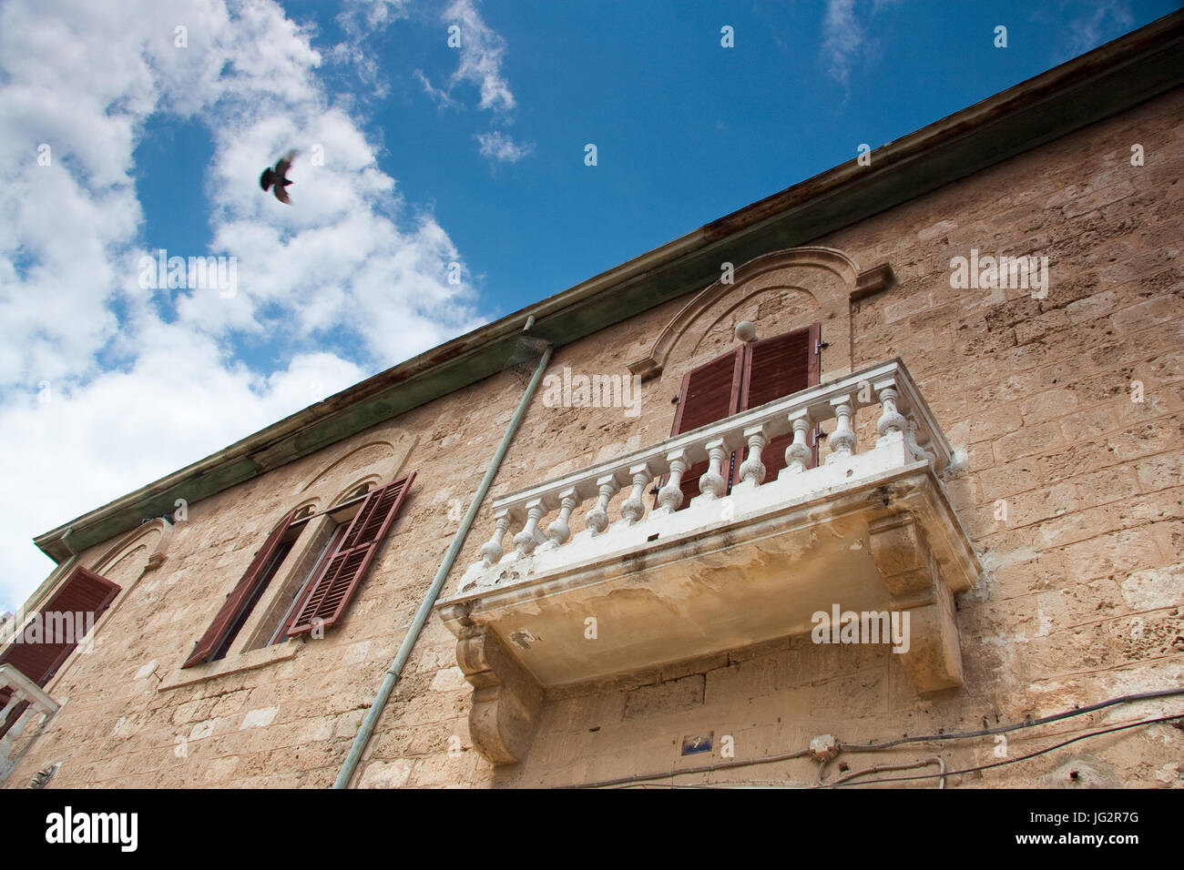 Traditional building with windows and balcony and overflying pigeon in Famagusta, Cyprus - Stock Image