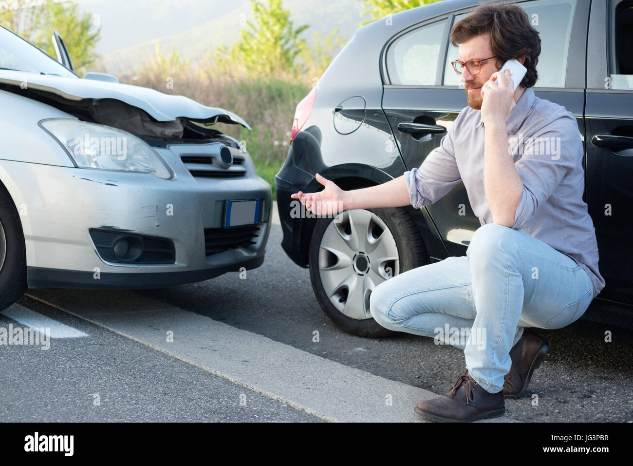 Man Calling Help After A Car Crash Accident On The Road Stock Photo