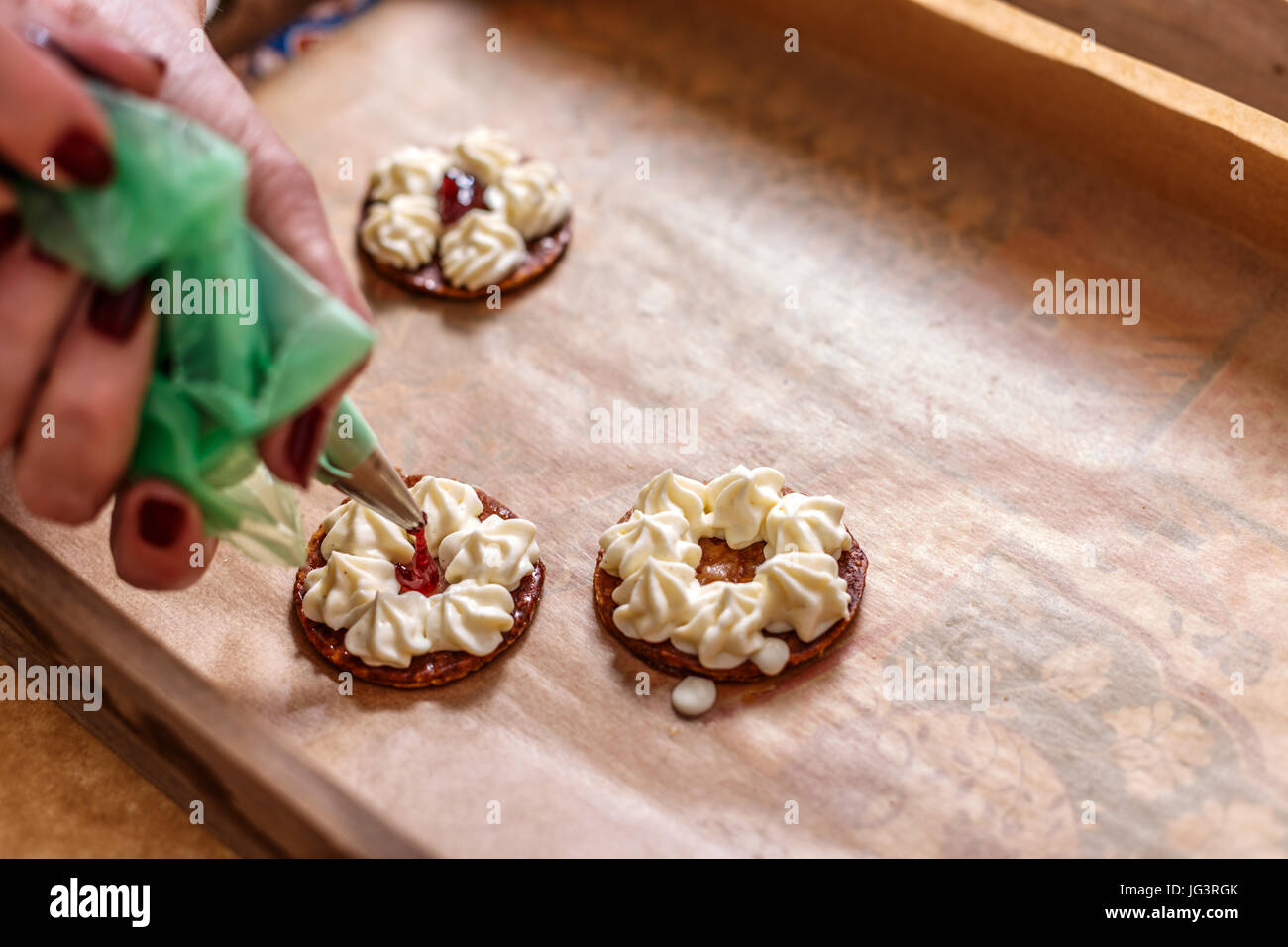 woman hand decorating mille feuille cake with jam stock photo