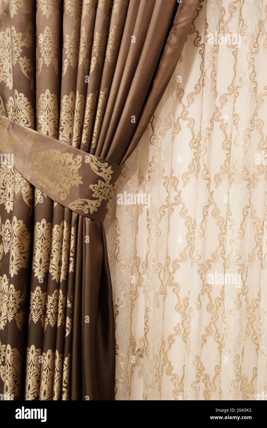 Part of beautifully draped curtain on the window in the room. Close up of piled curtain. Luxury curtain, home decor. - Stock Image