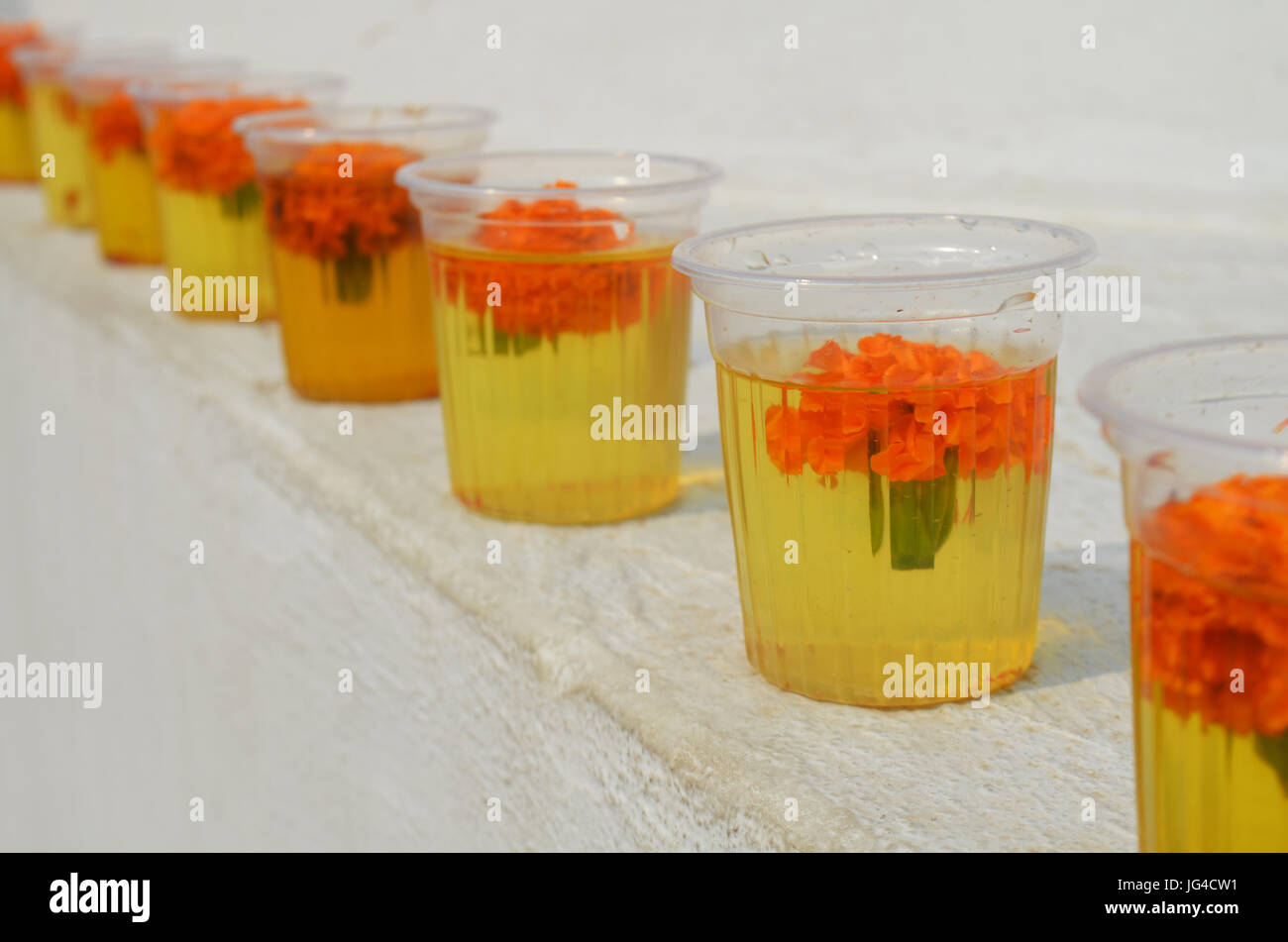 Glasses with water and carnation flowers at The Great stupa Bodnath in Kathmandu, Nepal. - Stock Image