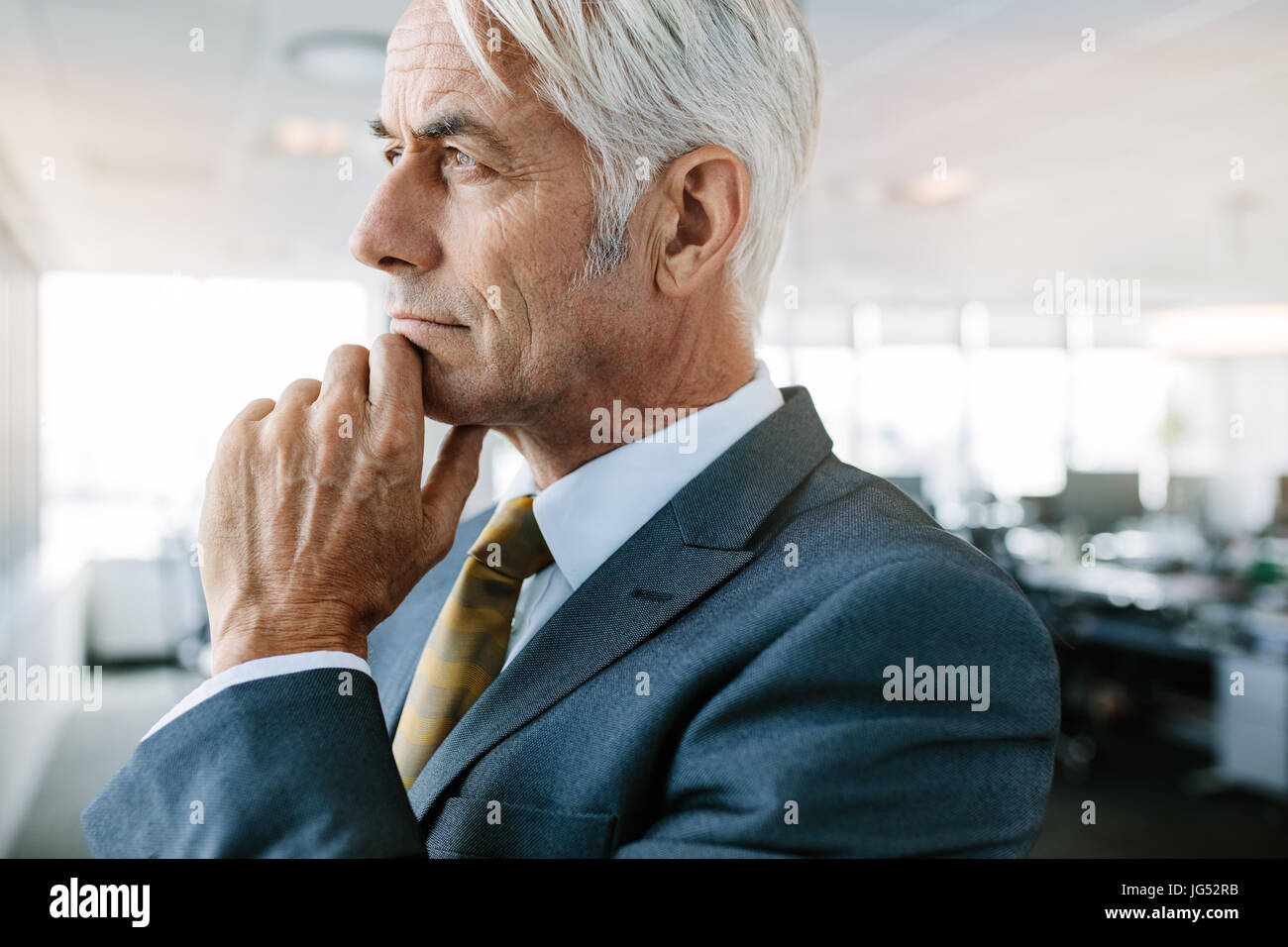Side view shot of mature businessman thinking with hand on chin. Closeup of senior caucasian entrepreneur looking - Stock Image