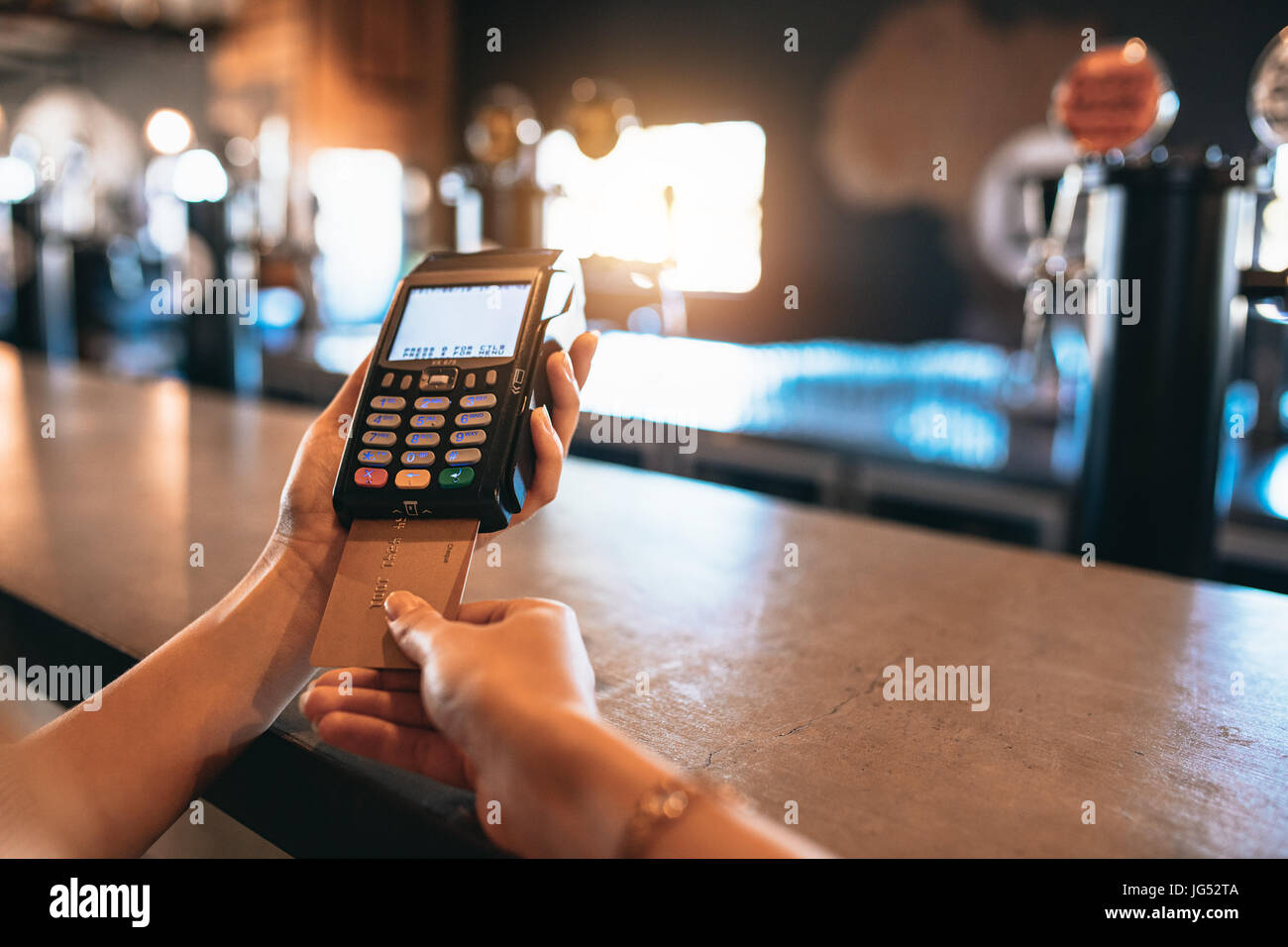 Hands of woman paying bill using a credit card at bar. Cropped shot of female at brewery factory doing cashless - Stock Image