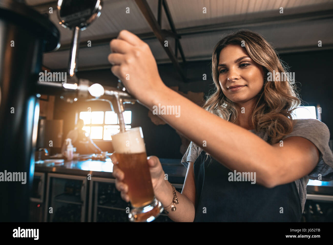 Young woman dispensing beer in a bar from metal spigots. Beautiful female bartender tapping beer in bar. - Stock Image