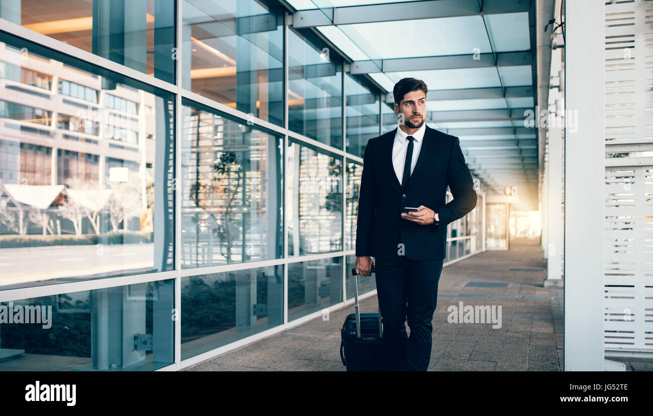 Handsome young businessman walking outside public transportation station. Caucasian business traveler with suitcase - Stock Image