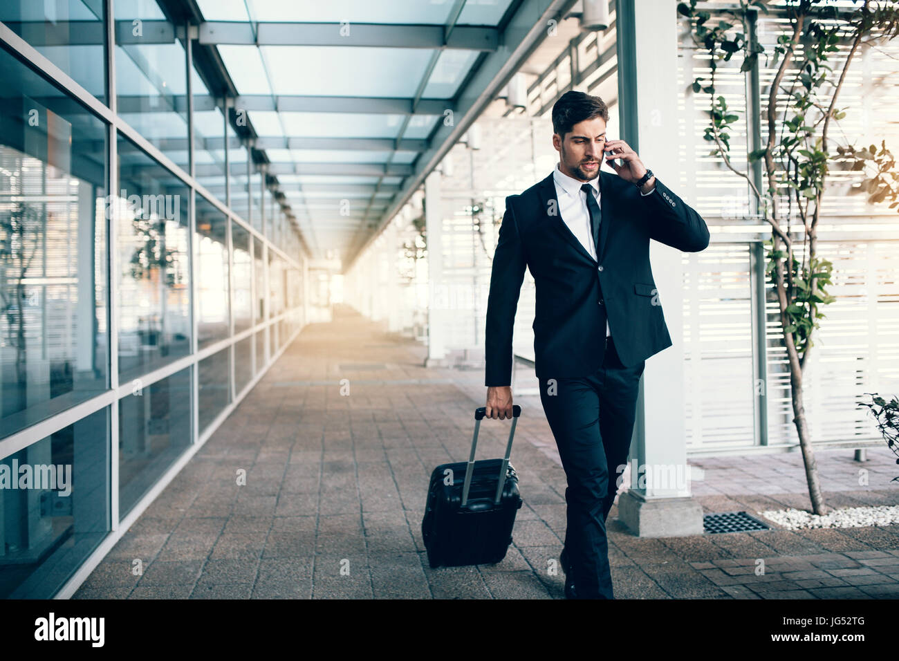 Handsome young man on business trip walking with his luggage and talking on cellphone at airport. Travelling businessman - Stock Image