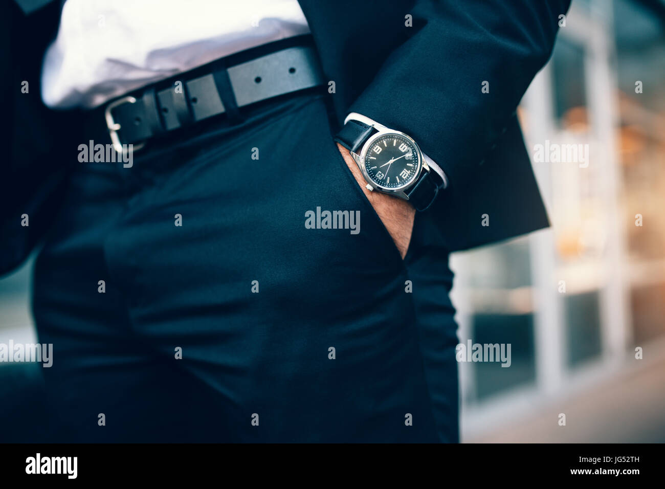 Close up of a business man's hand wearing a watch. Hand in pocket with wrist watch. - Stock Image