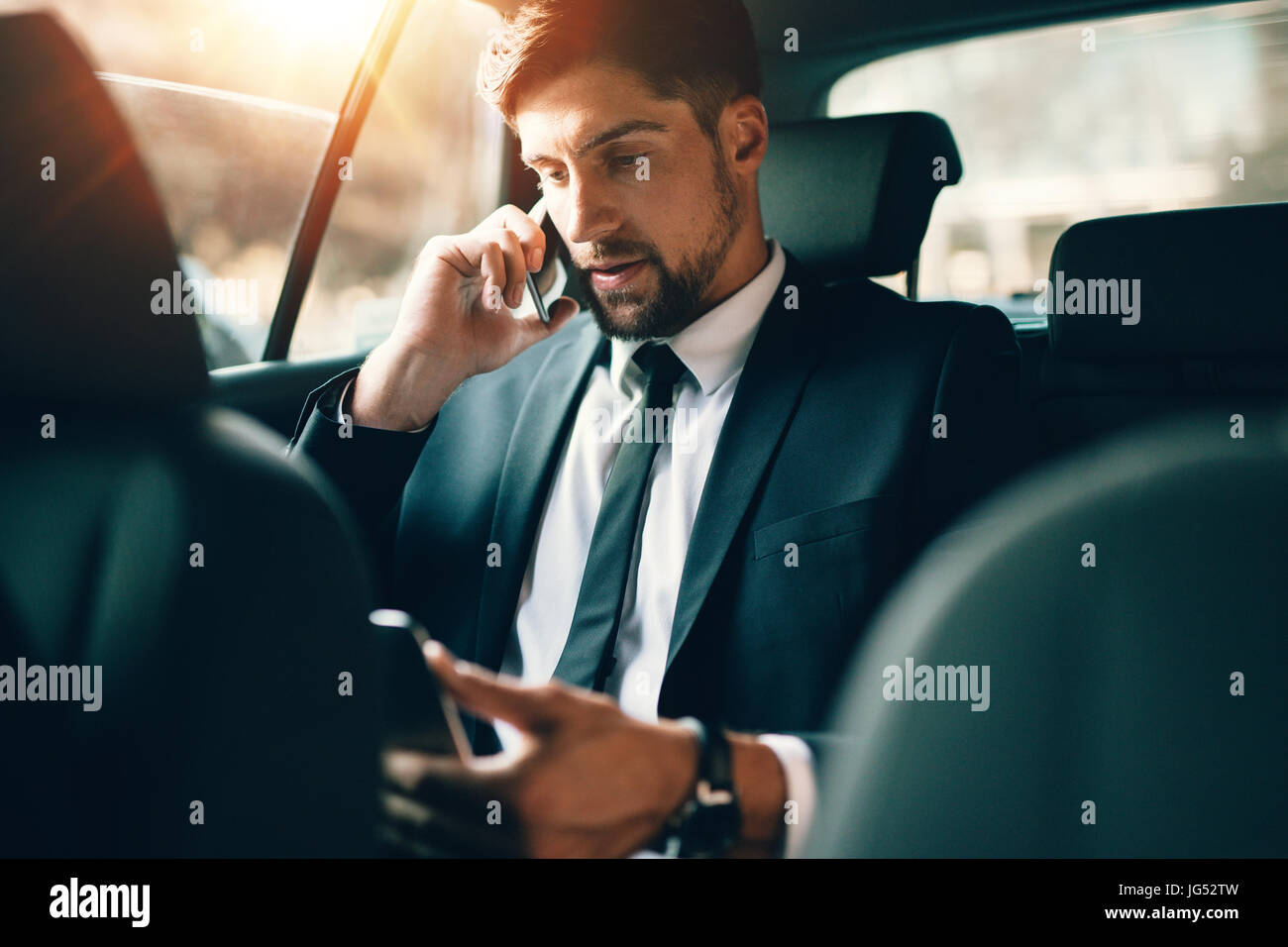 Young businessman talking on mobile phone and using tablet pc while sitting on back seat of a car. Caucasian male - Stock Image