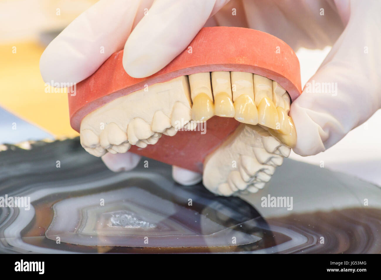 Dentures, prosthesis and oral hygiene. Hands with gloves while working on a dental prosthesis. Stock Photo