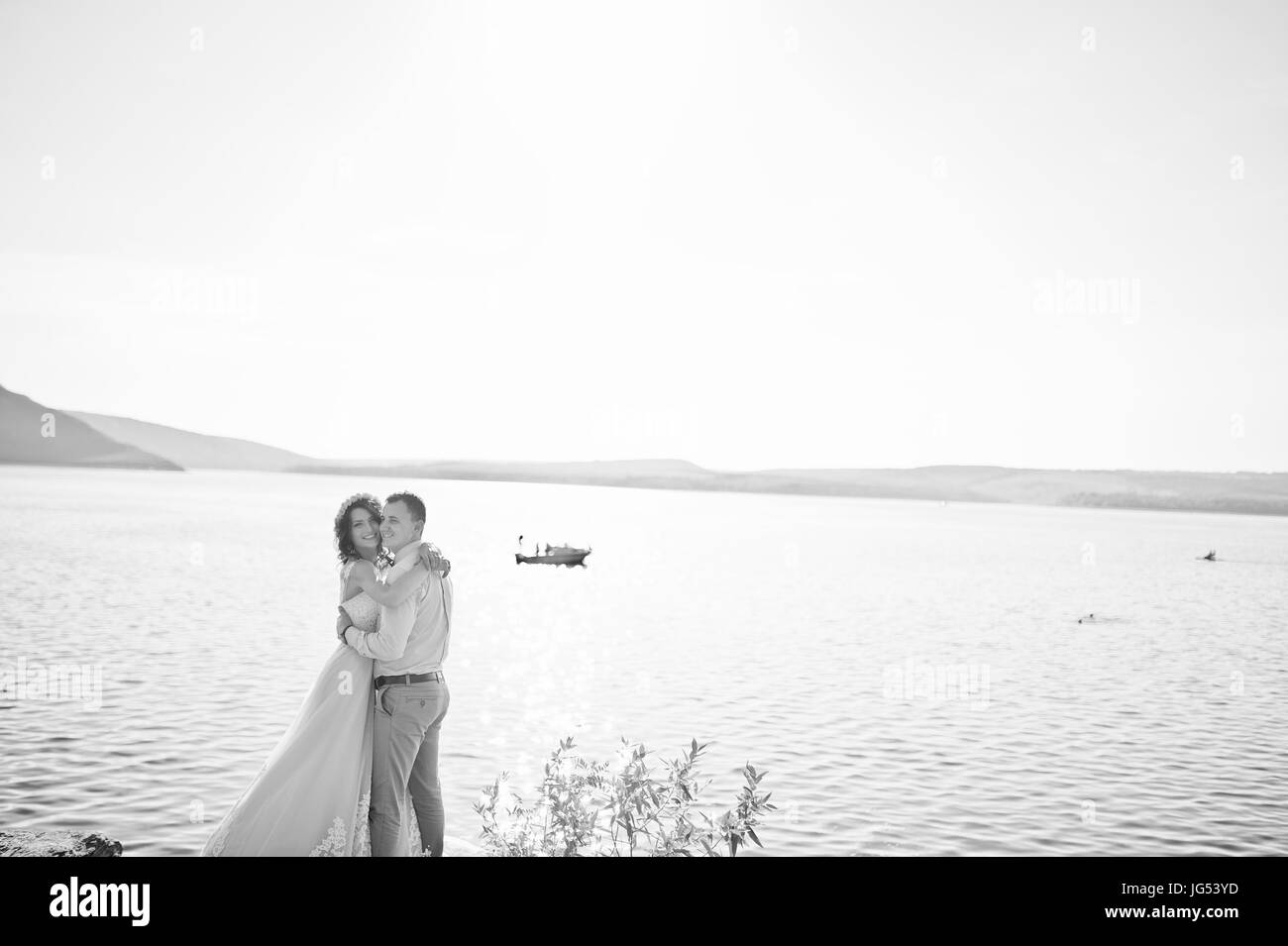 Newly married couple dancing on the rocky cliff with a view of a lake in the background on their wedding day. Black - Stock Image