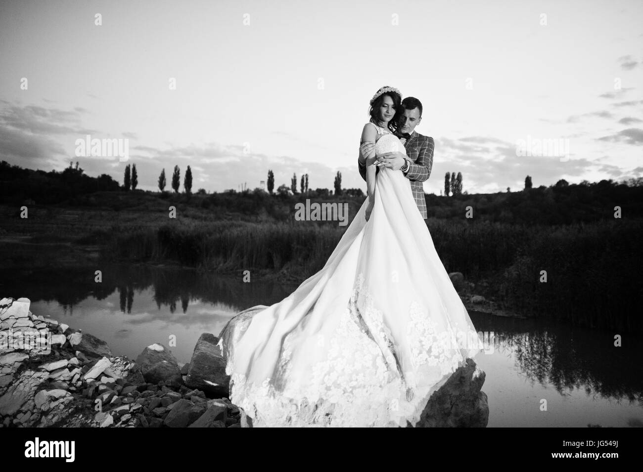 Beautiful wedding couple holding hands and looking at each other in the countryside next to the lake in the evening. - Stock Image