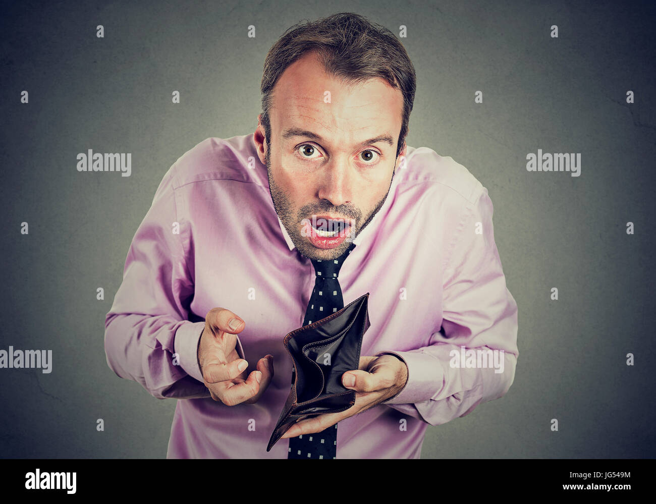 Man with no money. Businessman holding showing empty wallet - Stock Image