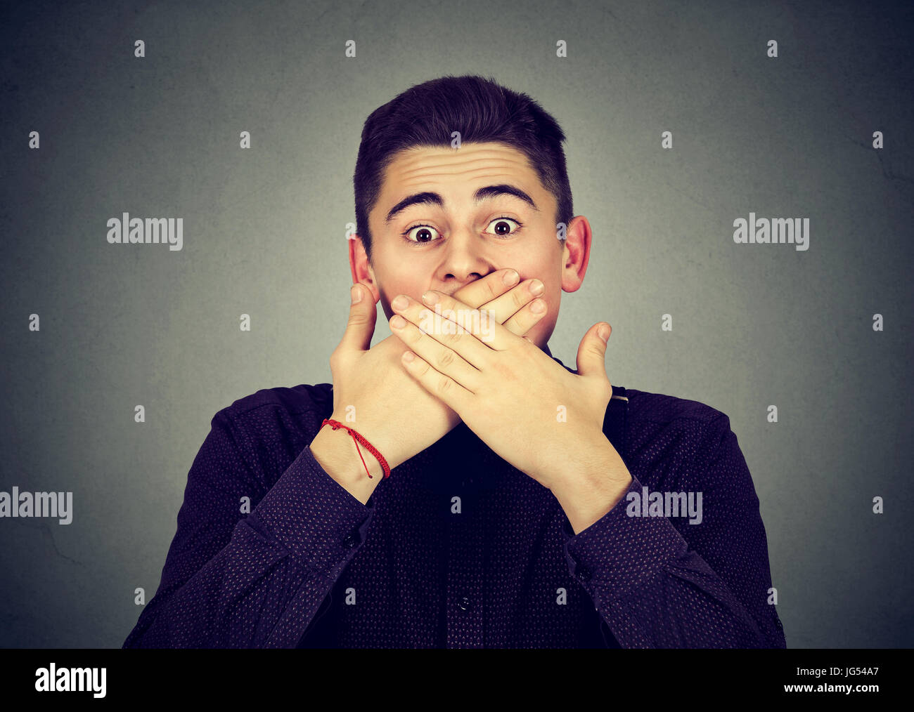 Scared man covering mouth with hands Stock Photo