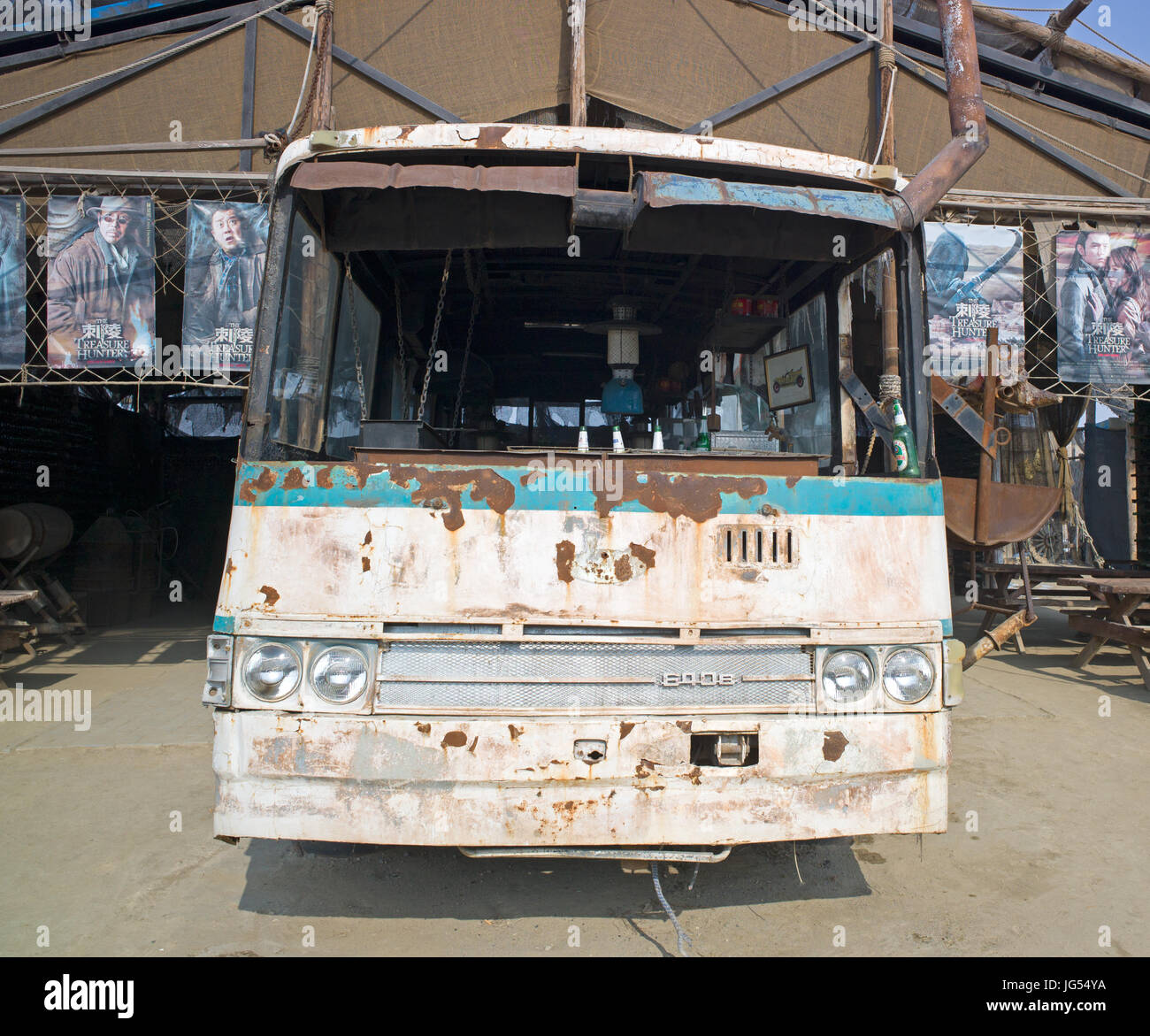 Rusting shell of bus used as temporary shelter and for stage prop, China West Film Studio, Ningxia - Stock Image