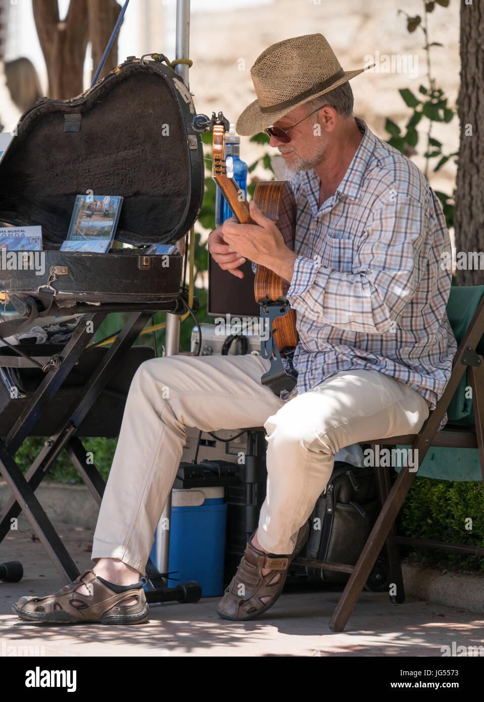 RONDA, SPAIN - JUNE 2017: A Street musician at work playing Flamenco guitar in Ronda, Spain Stock Photo