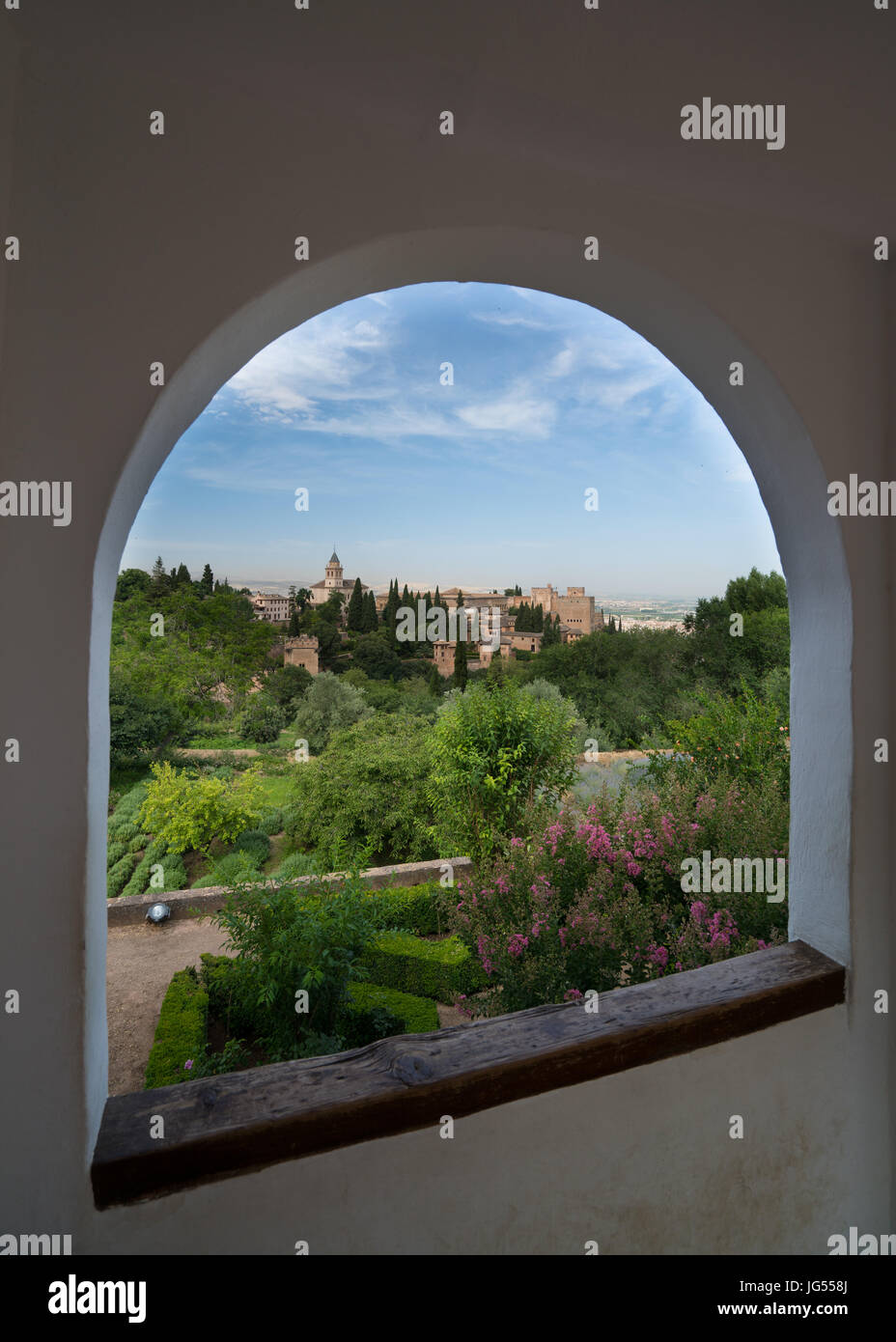 View throuh an arched window of Granada and the Alhambra Palace and fortress located in, Granada, Andalusia, Spain. Stock Photo