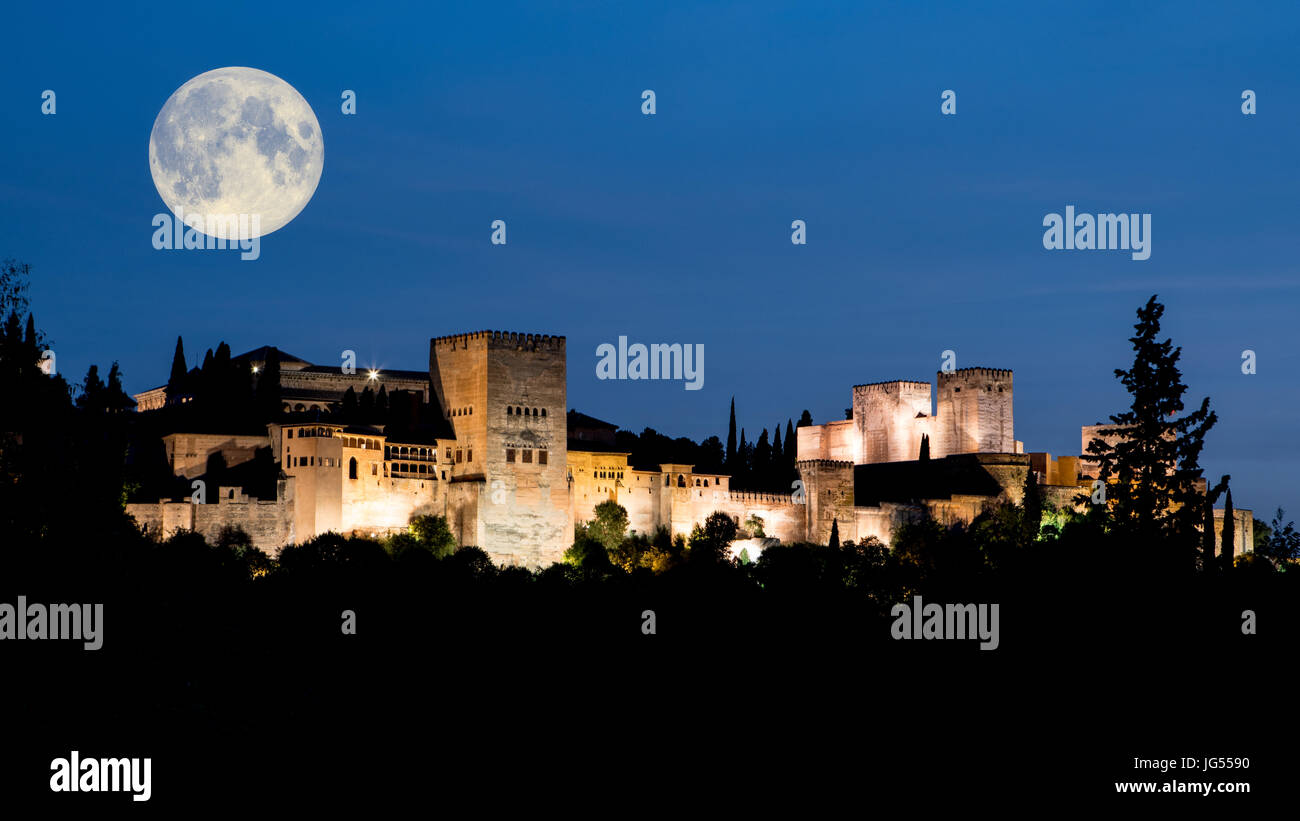 Early evening with full oon over the Alhambra Palace and fortress located in, Granada, Andalusia, Spain. Dark blue Stock Photo